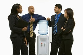 People standing at the water cooler. Used to illustrate The Language Lab's blog post Business Communication – When English Isn't Your First Language.
