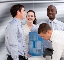 Workers at a watercooler to illustrate The Language Lab's blog post about Improving Business English Language Skills.