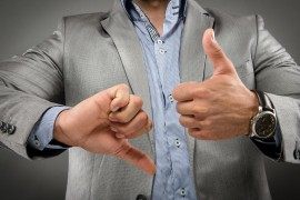 Man in suit jacket focused on hands, one hand is giving the thumbs up and the other is giving the thumbs down. Used to represent mixed messages.