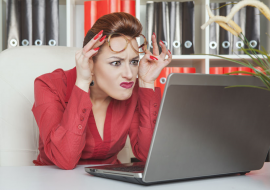 A woman looking at her computer with a RBF (resting bitch face).